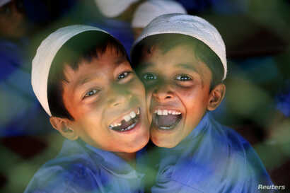 Rohingya refugee boys who study in an Islamic school smile as they react to the camera at a refugee camp in Cox's Bazar,…