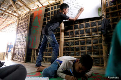 FILE PHOTO: Mohammed Tuahayran, 17, teaches English in a makeshift school at Kutupalong refugee camp in Cox's Bazar, Bangladesh…