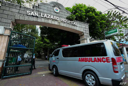 An ambulance enters the main gates of the San Lazaro Hospital in Manila, Philippines, Feb. 2, 2020. The Philippines reported the first death outside of China from the coronavirus, deepening global fears about an epidemic.