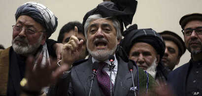 Afghan presidential candidate Abdullah Abdullah, center, addresses the media following a conference with his party members, in…