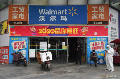 Workers are seen at an entrance to a Walmart store in Wuhan, the epicentre of the novel coronavirus outbreak, Hubei province, China, Feb.25, 2020.