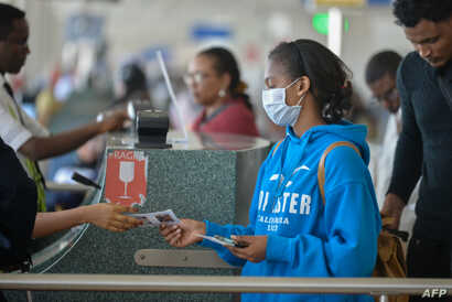 A passenger wears a mask as she waits at passport control in Bole International Airport in Addis Ababa, on January 30, 2020,…