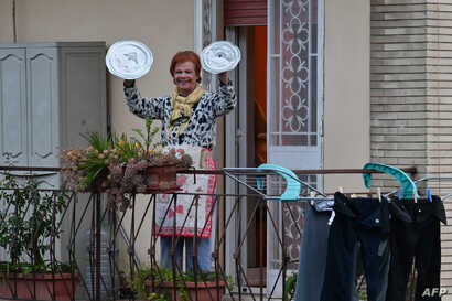 """A residents uses pot lids to play cymbals as she takes part in a music flash mob called """"Look out from the window, Rome mine !""""…"""