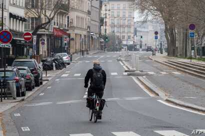 A man rides his bicycle along an empty street in Paris, on March 20, 2020 as a strict lockdown comes into effect to stop the…