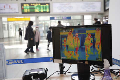 A thermal camera monitor shows the body temperature of people at the Seoul Railway Station in Seoul, South Korea, March 2, 2020.
