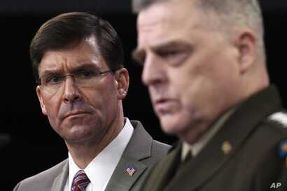 Defense Secretary Mark Esper, left, listens as Chairman of the Joint Chiefs of Staff Army Gen. Mark Milley, right, speaks…