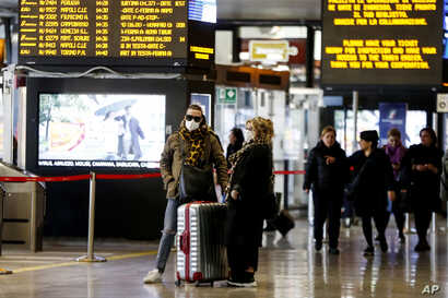 Travelers wear face mask as they wait at the Termini train station in Rome, March 8, 2020.