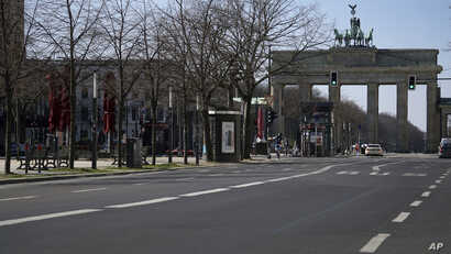 An almost empty road leads towards the Brandenburg Gate in Berlin, Germany, Tuesday, March 24, 2020. In order to slow down the…