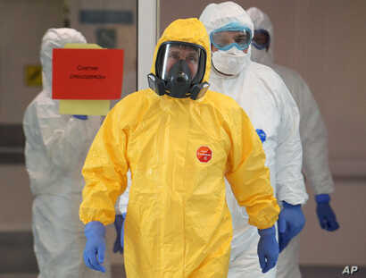 Russian President Vladimir Putin, center, wearing a protective suit enters a hall during his visit to the hospital for…