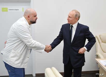 Russian President Vladimir Putin, right shakes hands with the hospital's chief Denis Protsenko during his visit to the hospital…