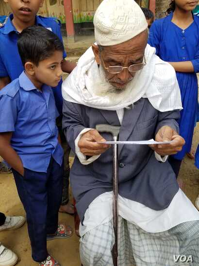 Abdul Hakim tries out new eyeglasses at a school in Rajapalong, a community in southeastern Bangladesh's poor Cox's Bazar district. (Carol Guensburg/VOA)