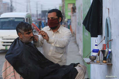 A barber wears a protective mask as a preventive measure amid coronavirus fears, as he gives a haircut to a customer along a…