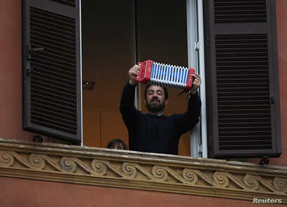 A man plays accordion as he looks out of an apartment window as part of a flashmob organised to raise morale during Italy's…