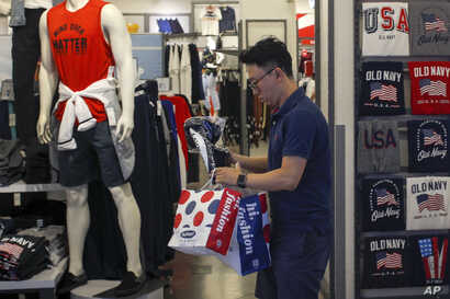 FILE - A man buys clothes from an American clothing store at a shopping mall in Beijing, China, July 15, 2019.