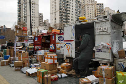 Delivery workers sort outaDelivery workers sort out parcels piling up at a pickup point outside residential apartment buildings closed off to non-residents following the coronavirus outbreak in Beijing, March 2, 2020.parcels piling up at a pickup point outside residential apartment buildings closed off to non…