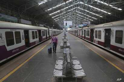 A man wearing a mask walks through a deserted train station in Mumbai, India, March 22, 2020.