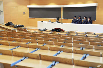 Examiners sit in an empty classroom as they listen to students defending their thesis on line, at the Politecnico University in Milan, Italy, March 5, 2020.