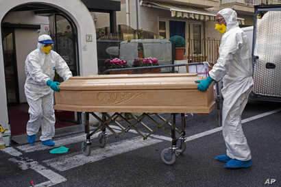 Medical staff wearing protective suits carry the coffin containing the body of Assunta Pastore, 87, after she passed away in her room at the Garden hotel in Laigueglia, northwest Italy, Liguria region, March 1, 2020.