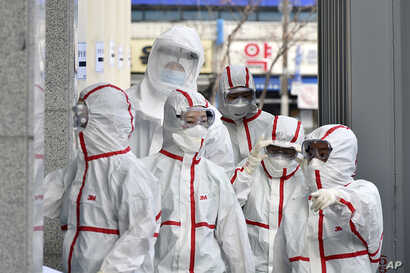 Medical staff members in protective gears arrive for a duty shift at Dongsan Hospital in Daegu, South Korea, March 3, 2020.
