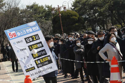 An employee holds a board with information of face mask sales as people line up to buy face masks to protect themselves from the new coronavirus outside Nonghyup Hanaro Mart in Seoul, South Korea, March 5, 2020.