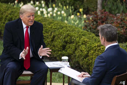 President Donald Trump talks with host Bill Hemmer during a Fox News virtual town hall with members of the coronavirus task force, in the Rose Garden at the White House, March 24, 2020, in Washington.