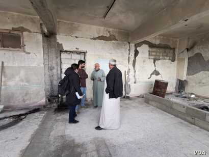 Ahmed Hashem was displaced from his home in Idlib, Syria, several times. Here, he speaks to Heather Murdock and Halan Akoiy in a complex refugees now occupy after it was abandoned by IS militants, in Raqqa, Syria, Feb. 23, 2020. (Hamodi JwanKojo/VOA)