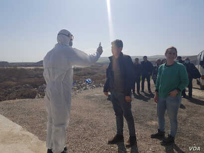 Workers scan travelers for signs of fever as they enter Iraq Feb. 27, 2020, only hours before Syria closed its side of the border. (Heather Murdock/VOA)