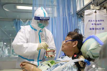 A nurse in a protective suit feeds a novel coronavirus patient inside an isolated ward at Zhongnan Hospital of Wuhan University, during the Lantern Festival, in Wuhan, Hubei province, China, Feb. 8, 2020.