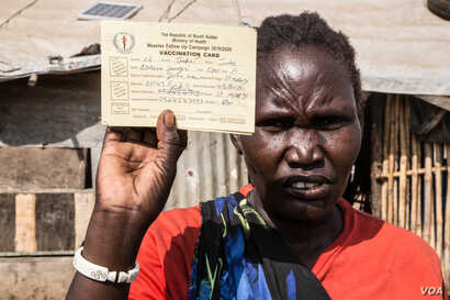 Shejirina Moni shows her measles vaccination immunization card for one of her children. Her children were vaccinated against measles in February as part of a nationwide campaign. (Chika Oduah/VOA)