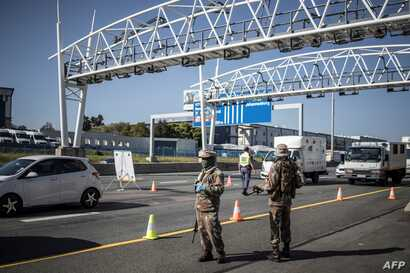 South Africa soldiers are seen at a checkpoint managed by the South Africa Police Services on the N1 highway in Johannesburg,…