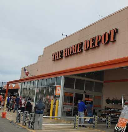 "Customers maintain ""social distancing"" while waiting in line to get into a Home Depot in Alexandria, Virginia that is limiting t"