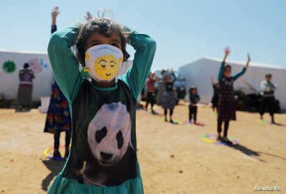 A displaced girl wears a face mask as she takes part in an event organzied by Violet Organization, in an effort to spread…