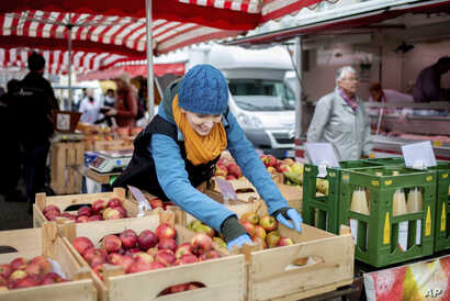 A saleswoman takes apples from a crate at the weekly market in Germany.