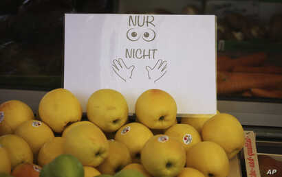 "A sign  describes ""Only look, do not touch"" is display near fruits at the city market in Augsburg, Germany, Monday, March 23,…"