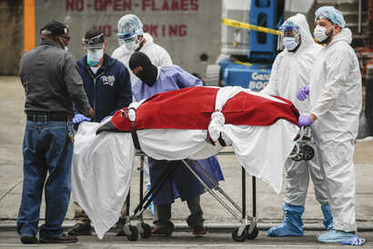 A body wrapped in plastic is unloaded from a refrigerated truck by medical workers wearing personal protective equipment due to COVID-19 concerns, March 31, 2020, at a hospital  in  New York.