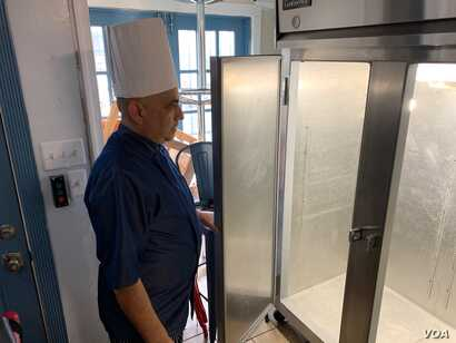 Chef Velazquez looks into an empty refrigerator that use to be full of meals he supplied to schools and day care centers. (C. Simkins/VOA)