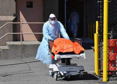 A medical staffer moves the body of a coronavirus victim from the Wyckoff Heights Medical Center to a refrigerated truck, in Brooklyn, New York, April 2, 2020.