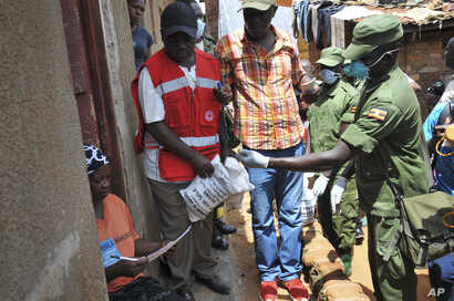 Member of the country's armed forces and a Red Cross worker distribute food to people affected by the lockdown measures aimed at curbing the spread of the new coronavirus, in the Bwaise suburb of the capital Kampala, Uganda, April 4, 2020.
