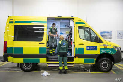 Paramedics clean and disinfect an ambulance after dropping a patient at the Intensive Care Unit (ICU) at Danderyd Hospital near…