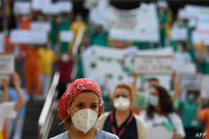 A healthcare worker takes part in a protest calling for a reinforced healthcare system outside the Gregorio Maranon hospital in…