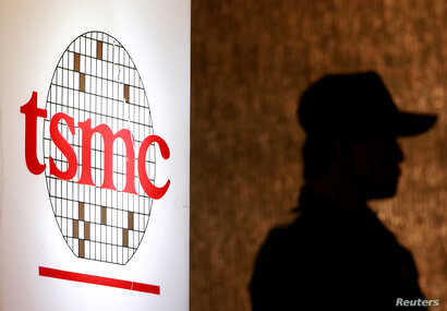 A security personnel stands near the logo of Taiwan Semiconductor Manufacturing Co. Ltd (TSMC) during an investor conference in…