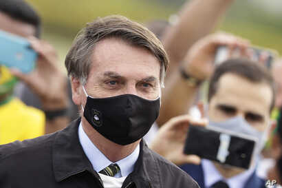 Brazil's President Jair Bolsonaro, wearing a face mask amid the new coronavirus pandemic, stands amid supporters taking…