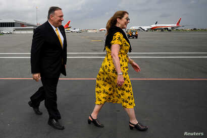 U.S. Secretary of State Mike Pompeo and his wife Susan Pompeo walk on the tarmac before departure at Luanda International Airport in Luanda, Angola, Feb. 17, 2020.