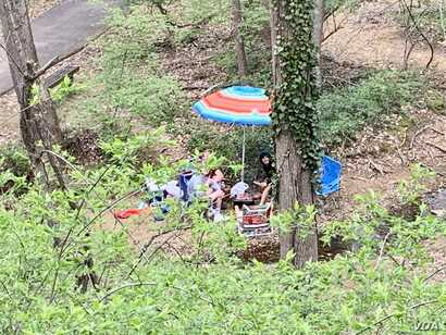 A family fired up a barbeque grill and sat on lounge chairs next to a creek to get a break from quarantine during COVID-19. (Carolyn Presutti/VOA)
