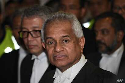 (FILES) In this file photo taken on July 04, 2018, Malaysia's Attorney-General Tommy Thomas (C) speaks to the media after former Malaysian prime minister Najib Razak appeared before a judge at the Duta court complex in Kuala Lumpur. Malaysia filed…