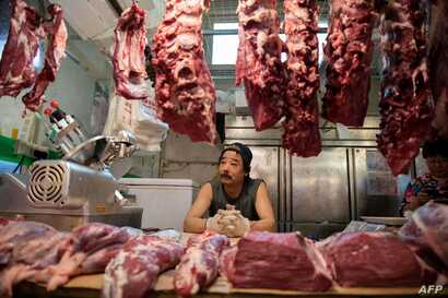 (FILES) This file photo taken on July 10, 2019 shows a butcher waiting for customers at his stall at a market in Beijing on July 10, 2019.  China is taking steps to boost pork supplies as prices soar ahead of a slew of upcoming holidays, including a…