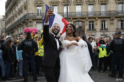 """A newly-wed couple take selfies pictures next to """"Yellow vest"""" protesters during an anti-government """"yellow vests"""" (gilets jaunes) protest in Paris on September 28, 2019.  / AFP / Zakaria ABDELKAFI"""