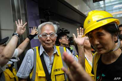 """This picture taken on September 7, 2019 shows """"Grandpa Wong"""" (centre L), 85, shielding protesters from the police by stepping between them along with other """"silver hair"""" volunteers in the Tung Chung district in Hong Kong. Despite his age, Wong is a…"""