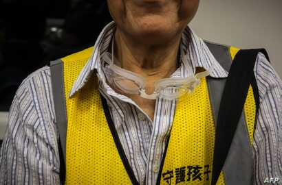 """This picture taken on September 7, 2019 shows a pair of swimming goggles dangling from the neck of """"Grandpa Wong"""", 85, as he rides an MTR train to the Tung Chung district in Hong Kong. Despite his age, Wong is a regular sight at Hong Kong's street…"""