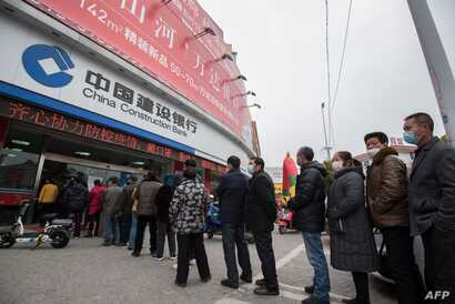 This photo taken on February 25, 2020 shows customers lining up to have their temperature taken before entering the bank in…